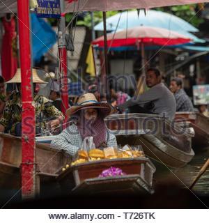Frau mit zwei Hüte in schwimmenden Markt - Stockfoto