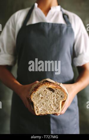 7/8 Schuß von Frau Baker in Uniform Holding frisches Brot. Frau Bäcker ein Brot Brot in der Bäckerei. - Stockfoto