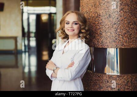 Closeup Portrait von freundlichen, lächelnden zuversichtlich Ärztin, Healthcare Professional in Scrubs mit Stethoskop, im Krankenhaus Flur stehenden b - Stockfoto