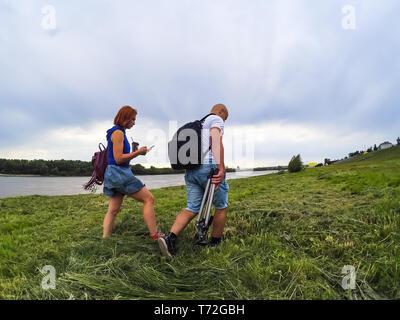 Der Mann und das Mädchen in Shorts und T-Shirts auf hohen grünen Gras am Flussufer mit Rucksäcken. Eine Frau hat Kaffee und ein Telefon in ihre Hände, - Stockfoto