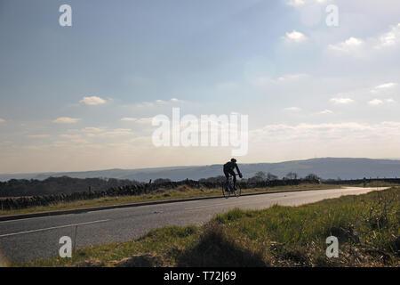 Radfahrer reiten entlang einer Landstraße in den Peak District, mit Hügel in der Ferne - Stockfoto