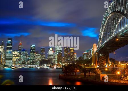 Seitliche Sicht auf die Sydney Harbour Bridge architektonische Sehenswürdigkeit und die Stadt bei Sonnenuntergang. Beleuchtete Bogen der Brücke in verschwommen Wasser Sydney, New widerspiegelt - Stockfoto