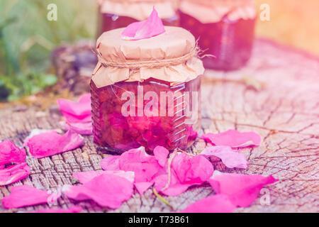 Stau in Rose mit Rosenblüten auf einem hölzernen Stumpf. Noch immer leben im Freien - Stockfoto
