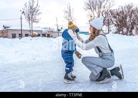 Eine junge Mutter richtet die Junge ihres Sohnes. Im Winter in der Stadt auf der Eisbahn. Im Winter Kleidung Eislauf, auf einem Hintergrund von Schnee. Freier Speicherplatz für - Stockfoto