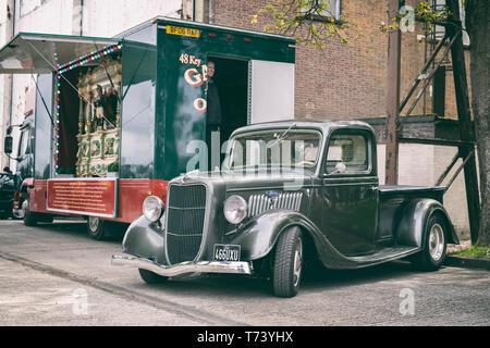 1936 Ford Pick up Truck vor einem viktorianischen Messe Orgel im Bicester Heritage Center, 'Drive es Tag'. Bicester, Oxfordshire, England. - Stockfoto