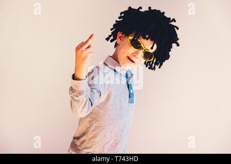 Kind gekleidet in lustige Perücke zeigt Mittelfinger zu lachen, isolierten weißen Hintergrund. - Stockfoto