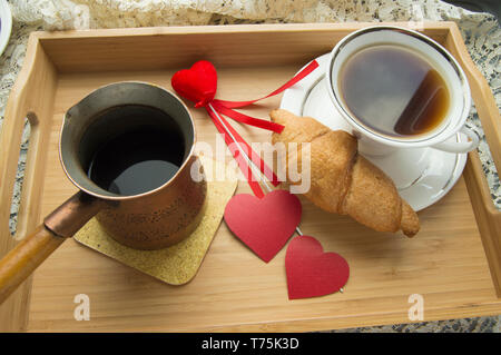 Valentinstag Frühstück Croissant und Kaffee ist in einem Fach mit Herz serviert. - Stockfoto
