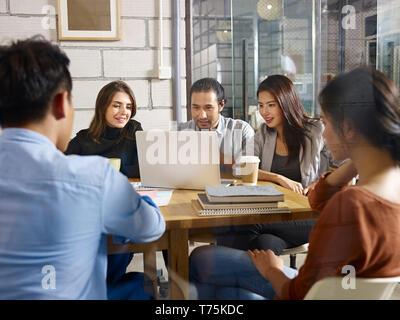 Gruppe von fünf Unternehmer Unternehmer asiatische und kaukasischen Männern und Frauen treffen im Unternehmen Office mit Laptop Computer. - Stockfoto