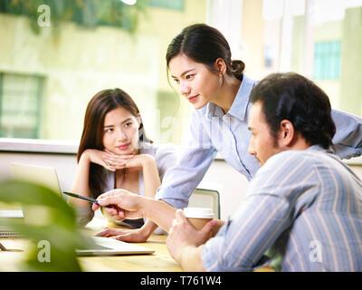 Drei jungen asiatischen Mannschaftskameraden Geschäftsleute Konferenz diskutieren, die im Büro, den Schwerpunkt auf die Person in der Mitte. - Stockfoto