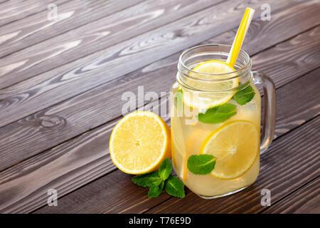 Frische Limonade im Marmeladenglas mit Stroh auf einem Holztisch - Stockfoto