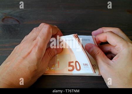 Closeup Mann Hände zählen 50 Euro-banknoten auf dunklen Holztisch - Stockfoto