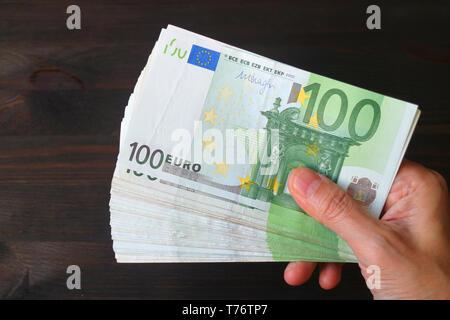 Blick von oben auf die männliche Hand, die eine Reihe von 100-Euro-Banknoten auf Dunkelbraunen hölzernen Tisch - Stockfoto