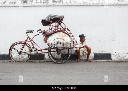 Treiber der Rikscha Fahrrad Taxi, sitzt auf Kandare in der Straße warten auf Passagiere, die für eine Fahrt bezahlt werden