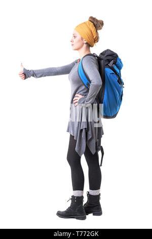 Seitenansicht des coolen Hipster junge Frau mit Rucksack, per Anhalter und Wegsehen. Voller Körper auf weißem Hintergrund. - Stockfoto