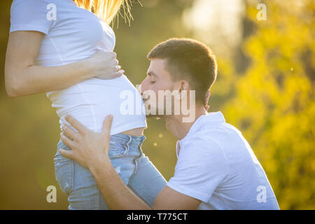 Glückliches Paar erwarten Baby, glücklicher Mann küssen Bauch der schwangeren Frau, junge Familie und das neue Leben Konzept - Stockfoto