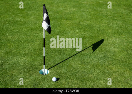 Golfball auf Putting Green weiter zu Bohrung und Flagge, sonnigen Morgen - Stockfoto