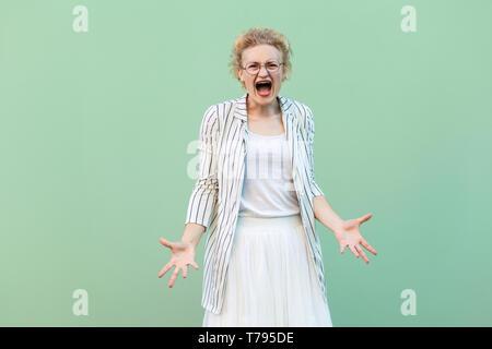 Was wollen Sie? Portrait von wütenden jungen blonden Frau in weißem T-Shirt, Rock, und gestreifte Bluse mit Brille stehen und Schreien mit angehobenem Ar - Stockfoto