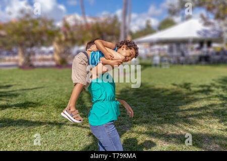 Mama nimmt das Kleinkind über die Schulter. Er genießt die Natur mit seiner Mutter lachte laut, als Sie geht mit ihm auf die Schulter. - Stockfoto