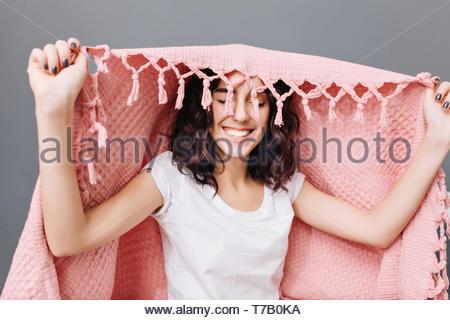 Portrait freudige Junge brünette Frau in Pyjama Spaß unter Rosa Decke auf grauen Hintergrund. Lächelnd mit geschlossenen Augen, Ausdruck true positive Emotionen, Entspannung zu Hause - Stockfoto