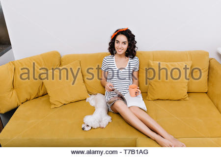 Wochenenden, freie Zeit erstaunlich hübsche junge Frau mit Brünette lockige Haare schneiden Lächeln auf Orange Sofa im Wohnzimmer. Chillen mit einem Hund, lesen Magazine, Home - Stockfoto