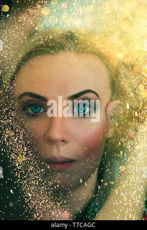 Porträt einer schönen jungen blonden Mädchen von Gold funkelt und leuchtet umgeben. Konzept: Neues Jahr, märchenhafte Welt, Kino. Schauspielerin erhält Make-up Bef