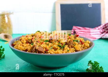 Bulgur mit Huhn und Gemüse. Leckeren, gesunden warmen Salat auf einem hellen Hintergrund. Bulgur Pilaw - Stockfoto