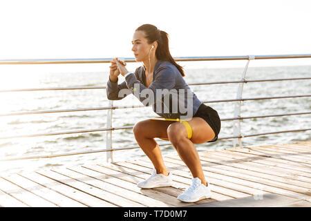 Konzentriert Sportlerin Übungen mit einem Gummiband am Strand - Stockfoto