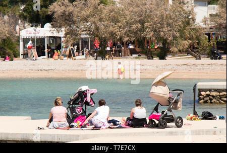 Vodice, Kroatien - 2. Mai 2019: Gruppe Mütter sitzen am Strand im Frühjahr Nebensaison mit Kinderwagen neben Ihnen - Stockfoto