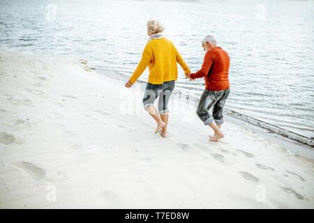 Schönes älteres Ehepaar in bunten Pullover zu Fuß am Sandstrand, genießen freie Zeit im Ruhestand in der Nähe des Meeres gekleidet. Ansicht von hinten - Stockfoto