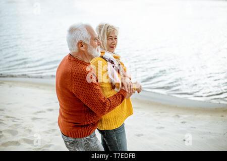 Schönes älteres Ehepaar in bunten Pullover umarmen am Sandstrand, genießen freie Zeit im Ruhestand in der Nähe des Meeres gekleidet - Stockfoto