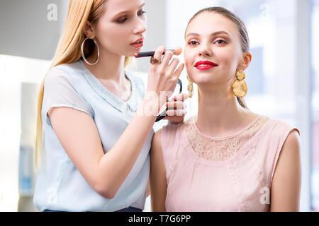 Positive fröhliche Frau, glücklich über ihr Make-up - Stockfoto
