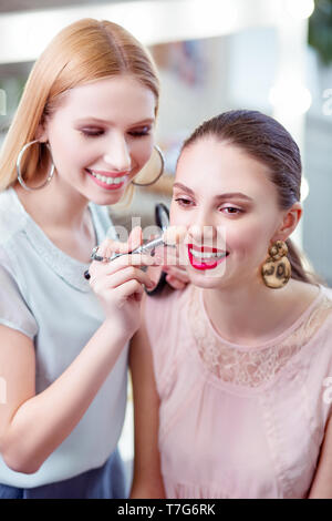 Freudige schöne Frau, die ihre Kunden Nase berühren mit einem Pinsel - Stockfoto