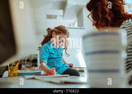 Mädchen mit Denim Kleid malen auf die Tabelle der Mutter - Stockfoto