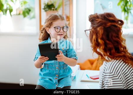 Tochter Gefühl aufgeregt besuchen Mama im Büro und mit Taschenrechner - Stockfoto