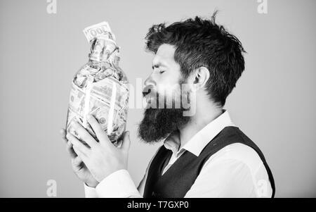 Geld Liebhaber. Brutale Geschäftsmann küssen Glas Glas mit Geld. Bärtiger Mann spart bares Geld im Sparschwein. Er ist gierig nach Geld. - Stockfoto