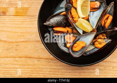 Eine Nahaufnahme von gekochten Muscheln mit Zitronenscheiben, Schuß von oben auf einen hölzernen Hintergrund mit einem Platz für Text - Stockfoto