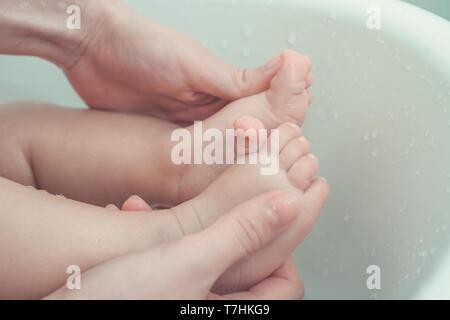 Mutter Holding und der Massage baby Füße beim Baden in der Badewanne. vintage Foto und Film Stil. - Stockfoto