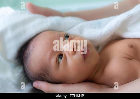 Asiatische baby Junge lächelnd und Gefühl glücklich nach der Badewanne. Mutter Trocknet und reibt ihr neugeborenes Baby Haare und den Kopf mit einem Handtuch nach einer Dusche. f