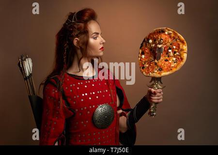 Schöne Frau im mittelalterlichen rote Tunika holding Dolch tragen mit lecker Pizza. Wunderschöne, tapferer Krieger mit Pfeilen hinter zurück, rote Lippen in Studio posieren. Konzept der Junk Food.