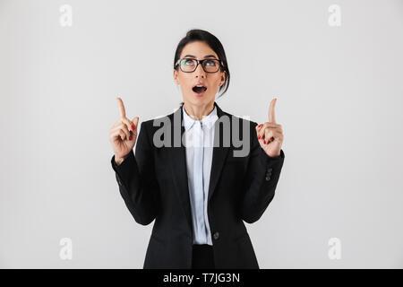 Portrait von niedlichen Geschäftsfrau 30 s in formalen Verschleiß und Brillen Pointing Finger nach oben auf weißem Hintergrund - Stockfoto