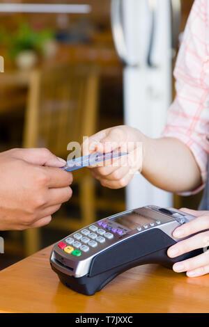 Kunden Hand Holding und die Zahlung für die Bestellung mit Kreditkarte im Cafe und Restaurant. Credit Card Payment Service. Kunde oder Kellner Eingeben von Code - Stockfoto