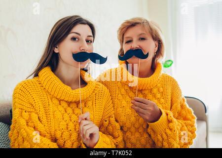 Ältere Mutter und ihre erwachsene Tochter unter selfie mit Cat mit Photo Booth Requisiten zu Hause. Muttertag Konzept. Spaß - Stockfoto