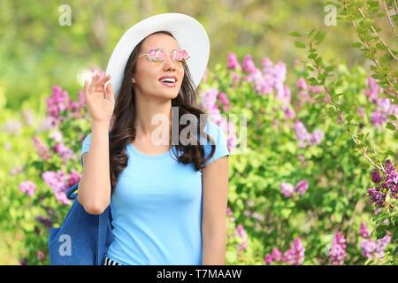 Schöne junge Frau mit Hut in der Nähe von blühenden Strauch an sonnigen Frühlingstag - Stockfoto
