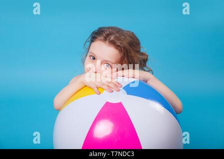 Wenig lächelnde Mädchen im Badeanzug mit großen aufblasbaren Ball auf blauem Hintergrund - Stockfoto