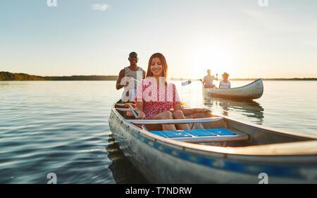 Lächelnden jungen Frau und ihr Freund paddeln Kanu mit einem anderen Paar in einem See an einem sonnigen Nachmittag - Stockfoto