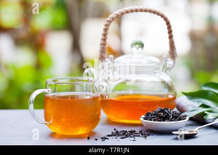 Schwarzer Tee im Glas Schale und Teekanne auf Sommer im Hintergrund. Kopieren Sie Platz. - Stockfoto