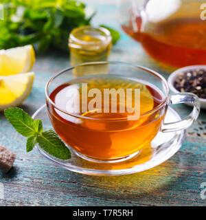 Tasse Tee mit Minze und Zitrone. Holz- Hintergrund. Close Up. - Stockfoto