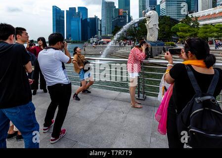 Touristen posieren für Fotos Vor dem Merlion Statue und die Skyline von Singapur, Singapur, Südostasien - Stockfoto