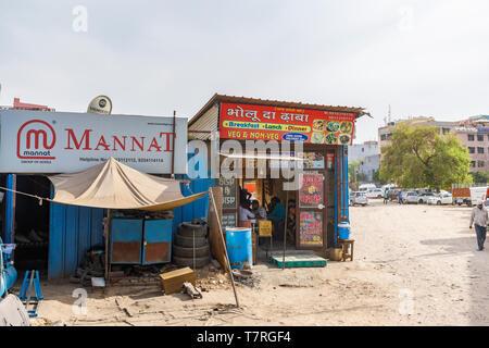 Straßenszene in Mahipalpur Bezirk, einem Vorort in der Nähe von Delhi Flughafen in New Delhi, die Hauptstadt Indiens: lokale Hotel, ein kleines Café und Parkplatz