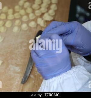Hände mit Blaue Handschuhe während der Produktion der italienischen frische Lebensmittel genannt Orecchiette ein typisches Gericht der Region Apulien in Süditalien - Stockfoto